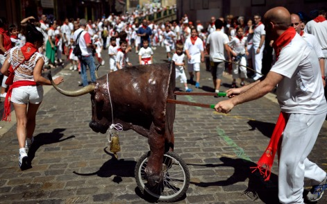 A woman runs in front of a toy bull during the Encierro Txiki on the fourth day of the San Fermin festival in Pamplona